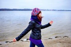Levensstijlportret van jonge Kaukasische slanke vrouwenlooppas langs de strandherfst Stock Afbeeldingen