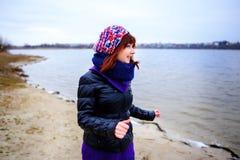 Levensstijlportret van jonge Kaukasische slanke vrouwenlooppas langs de strandherfst Royalty-vrije Stock Foto's
