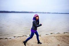 Levensstijlportret van jonge Kaukasische slanke vrouwenlooppas langs de strandherfst Stock Fotografie