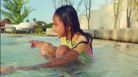 Levensstijlportret van mooi opgewekt en gelukkig kind die in leuk meisjeszwempak het vrolijke spelen met water in zwembad glimlac stock footage