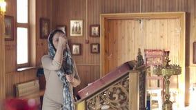 Levensstijlvrouw die in Kerk voor pictogrammen binnen bidden, Russische Orthodoxe houten Kerk, mening stock footage
