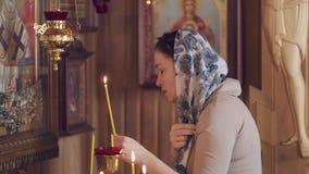Levensstijlvrouw die in Kerk voor pictogrammen binnen bidden, Russische Orthodoxe houten Kerk, mening stock videobeelden