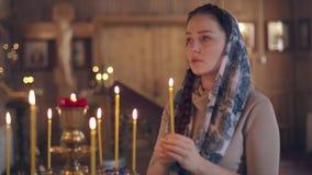 Levensstijlvrouw die in Kerk voor pictogrammen binnen bidden, Russische Orthodoxe houten Kerk, mening stock video