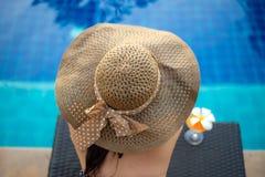 Levensstijlvrouw in zwempak die en gelukkig met cocktail op chaise-longue dichtbij zwembad ontspannen, de zomerdag Stock Afbeeldingen