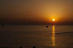 Lever de soleil à la mer calme avec un bateau image libre de droits