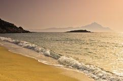 Lever de soleil à la plage près de la montagne sainte Athos, Chalkidiki Photo libre de droits