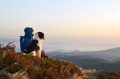 Lever de soleil admiratif de jeune femme et de chien haut dans la montagne Image libre de droits
