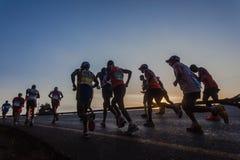 Lever de soleil ascendant de Silouettes de marathoniens Photos stock