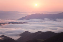 Lever de soleil au-dessus d'arête nuageuse de montagne Photo stock