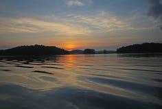 Lever de soleil au-dessus de l'eau de ondulation Images libres de droits