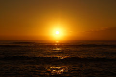Lever de soleil au-dessus de l'océan avec des vagues roulant vers le rivage Image libre de droits