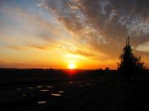 Lever de soleil au-dessus de la route et d'un sapin Photo stock