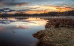 Lever de soleil au-dessus de lac brumeux Image libre de droits