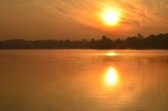Lever de soleil au-dessus de lac brumeux de ville image stock