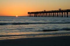 Lever de soleil au-dessus de pilier de plage de Jax Image stock
