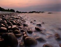 Lever de soleil au-dessus de plage de pavé rond Images stock