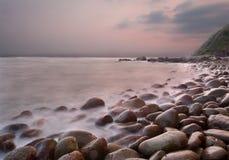 Lever de soleil au-dessus de plage de pavé rond Photo libre de droits