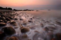 Lever de soleil au-dessus de plage de pavé rond Photos stock