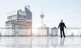 Lever de soleil au-dessus des gratte-ciel et de l'homme d'affaires faisant face au nouveau jour image stock