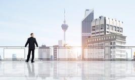 Lever de soleil au-dessus des gratte-ciel et de l'homme d'affaires faisant face au nouveau jour photo stock