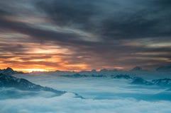 Lever de soleil au-dessus des nuages et des crêtes des alpes de Wallis Photographie stock libre de droits