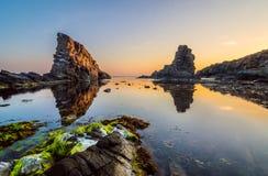 Lever de soleil au-dessus des roches de bateaux Images stock
