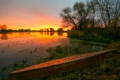 Lever de soleil au-dessus du lac avec la réflexion des arbres nus dans l'eau Photos stock