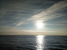 lever de soleil au-dessus de la mer calme Silhouette d'un petit bateau sur l'horizon Photos stock