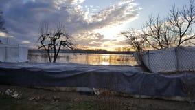 Lever de soleil au-dessus de la protection d'inondation de barrières de bac à sable photo stock