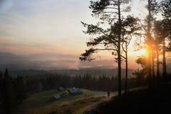 Lever de soleil au-dessus de la vallée brumeuse de haute montagne avec de vieilles maisons en bois sur une colline dans une forêt Photo libre de droits