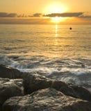 Lever de soleil avec des vagues se brisant au-dessus des roches Images libres de droits