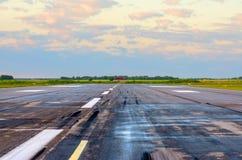 Lever de soleil avec l'aéroport de paysage de la piste humide avec des traces des pneus en caoutchouc sur l'asphalte Photographie stock