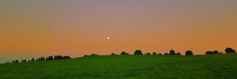Lever de soleil avec le clair de lune de la taille images libres de droits