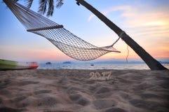 Lever de soleil avec le numéro en bois 2017 sur le fond tropical de plage Image stock
