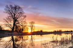 Lever de soleil avec les nuages colorés au-dessus d'un étang sauvage entouré par des arbres dans le matin d'automne Images libres de droits