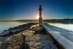 Lever de soleil avec sunstar au phare de Paquis, ville de Genève Photos stock