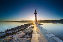 Lever de soleil avec sunstar au phare de Paquis, ville de Genève Photographie stock libre de droits