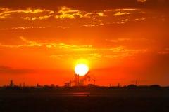 Lever de soleil brûlant au-dessus d'industrie de silhouette Photographie stock libre de droits