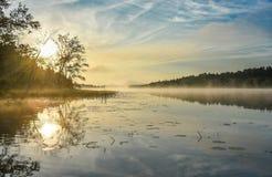 Lever de soleil brillant le matin brumeux et brumeux d'été sur le lac corry Image stock