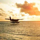 Lever de soleil d'été avec l'hydravion Hydravion d'atterrissage sur le bord de la mer Image libre de droits
