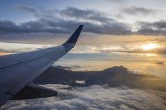 Lever de soleil d'un avion en vol avec la vue de son aile et du soleil derrière Image libre de droits