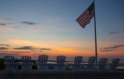 Lever de soleil dans Ogunquit Maine avec les chaises et le drapeau images stock
