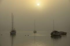 Lever de soleil de bateaux dans le brouillard images libres de droits