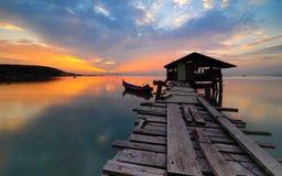 Lever de soleil de jetée au-dessus de l'océan avec le bateau de pêche à l'autoroute urbaine de Jelutong, Penang, Malaisie Image stock
