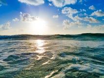 Lever de soleil de plage, ressac vert, nuages et ciel bleu Images libres de droits