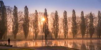 Lever de soleil de ressort avec des arbres au-dessus de canal de l'eau avec le pêcheur Photos stock