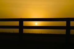 Lever de soleil derrière la barrière Photo stock