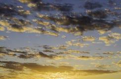 Lever de soleil dramatique avec le ciel orange et bleu et les nuages noirs Images stock