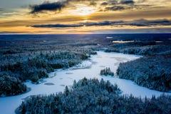 Lever de soleil en hiver tôt au-dessus d'un lac et d'une forêt image libre de droits