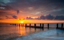Lever de soleil et protections côtières, Norfolk R-U Photos stock